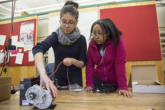 Two students work on an engineering project.