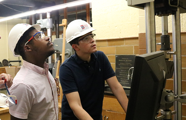 Two students looking at a machine