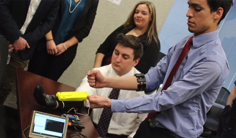student showing client hand-gripping device he invented